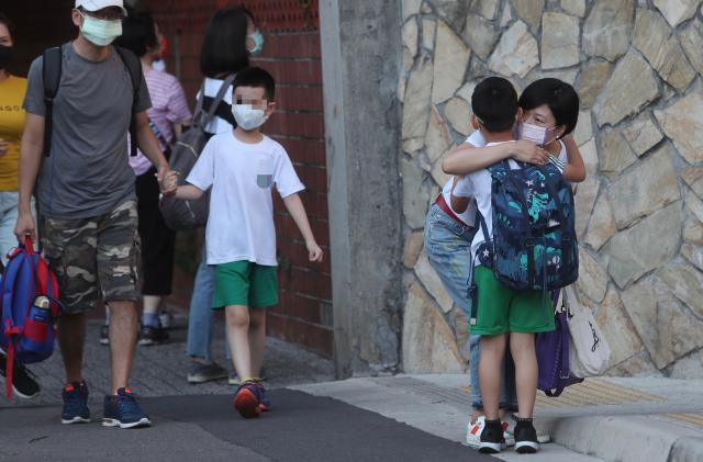 圖為10日板橋區一所國小復課,小朋友在校 門外與家長擁抱。(中央社)