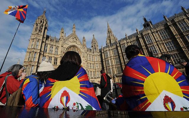 英國議員表示,中共大使利用自由社會的設施為其政權鼓譟,是不可想像的。圖為2009年3月10日,身披藏族雪山獅子旗的抗議者進入英國國會大廈。(Leon Neal/AFP via Getty Images)