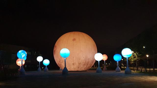 冬山火車站前廣場設置10米高月球及12顆小行星,陪你過中秋。(冬山鄉公所提供)