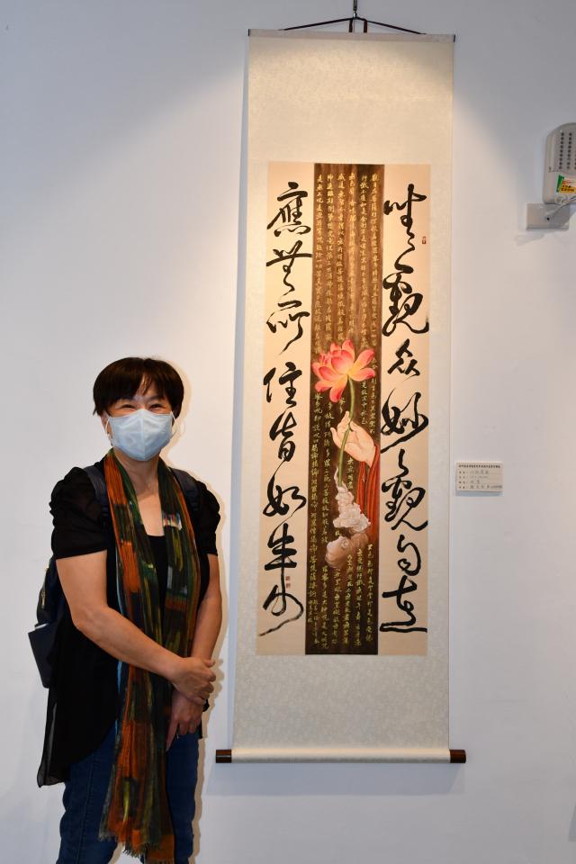 新竹縣美術協會前會長謝秀英與展出的水墨畫。