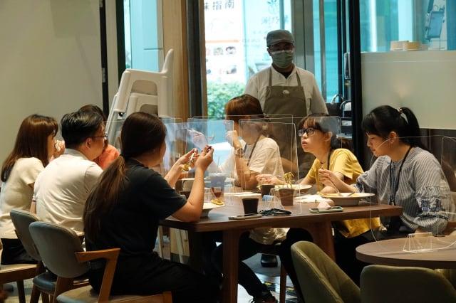 北市衛生局提醒,出外用餐仍要遵守實聯制,且同住家人同桌仍須保持1.5公尺間距或使用隔板。(中央社)